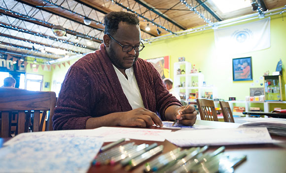 UNCG graduate Maurice Moore enjoys drawing at Geeksboro Coffehouse Cinema in Greensboro.